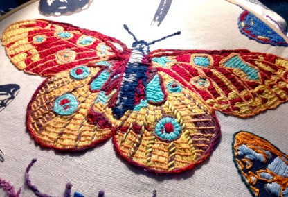 Bayeux Stitch Peacock Butterfly. Wool on linen tea-towel. Renata Bursten.
