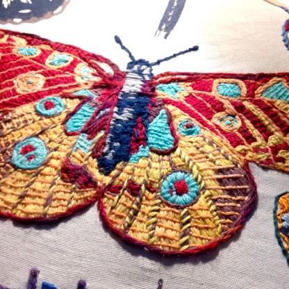 Bayeux Stitch Peacock Butterfly. Wool on linen tea-towel. Renata Bursten.